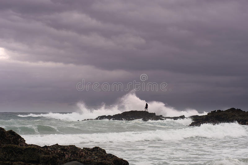 Download Man Looks For Shellfish On Rocks In Stormy Sea Stock Photos - Image: 11889933
