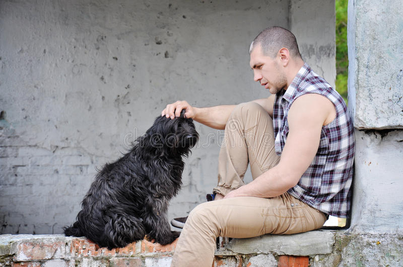 Man looks at a stray dog and keeps a hand on the dog's head. royalty free stock image