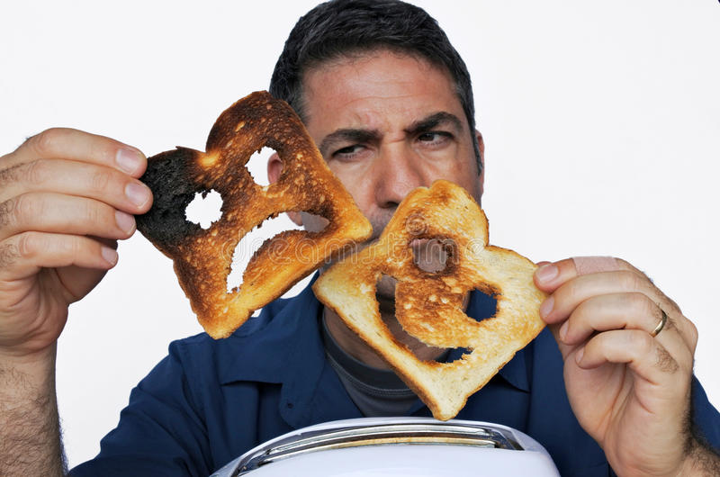 Man looks at two different slices of toast bread royalty free stock images