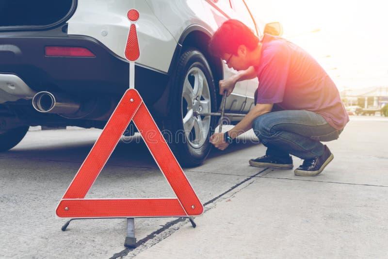 Man loosening lug nuts on his car flat tire. Broken down car stock photos