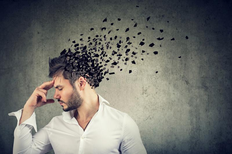 Man losing parts of head as symbol of decreased mind function. Memory loss due to dementia or brain damage. Side profile of a man losing parts of head as symbol stock images
