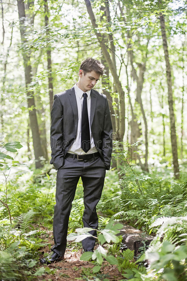 Man alone. A young man wearing a suit standing in the woods looking down royalty free stock photography