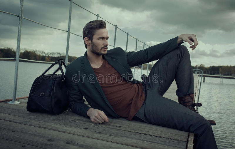 Man lounging on deck. A man lounging on a wooden deck royalty free stock images