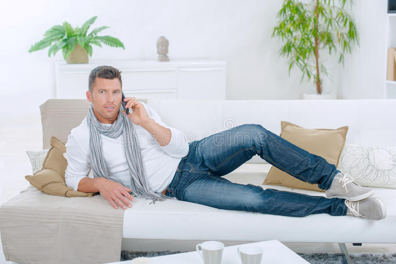 Man lounging on sofa. Man lounging on the sofa royalty free stock photography