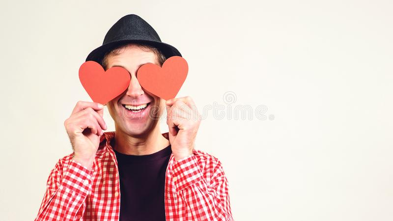 Man in love. Happy man covered his eyes by red hearts, isolated on white. Copy space. Happy Valentine day. Funny man in black hat royalty free stock photo