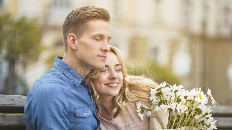 Man in love hugging beloved girlfriend, happy young lady holding nice flowers royalty free stock photos