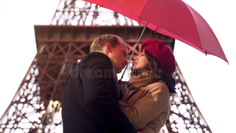 Man in love about to kiss beautiful woman under umbrella, romantic date in Paris stock photography