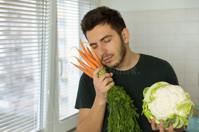 Conceptual photo about the benefits of proper nutrition. Man lovingly cuddles fresh vegetables. Conceptual photo about the benefits of proper nutrition stock images