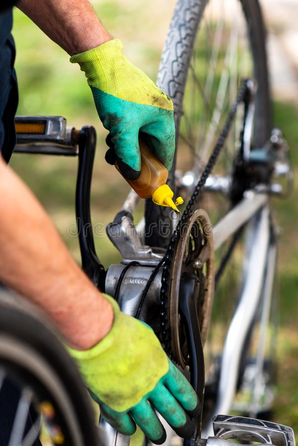 Man lubricating bicycle chain maintaining for the new season. Man lubricating bicycle chain and maintaining for the new season lube maintenance lubricate oil royalty free stock photos