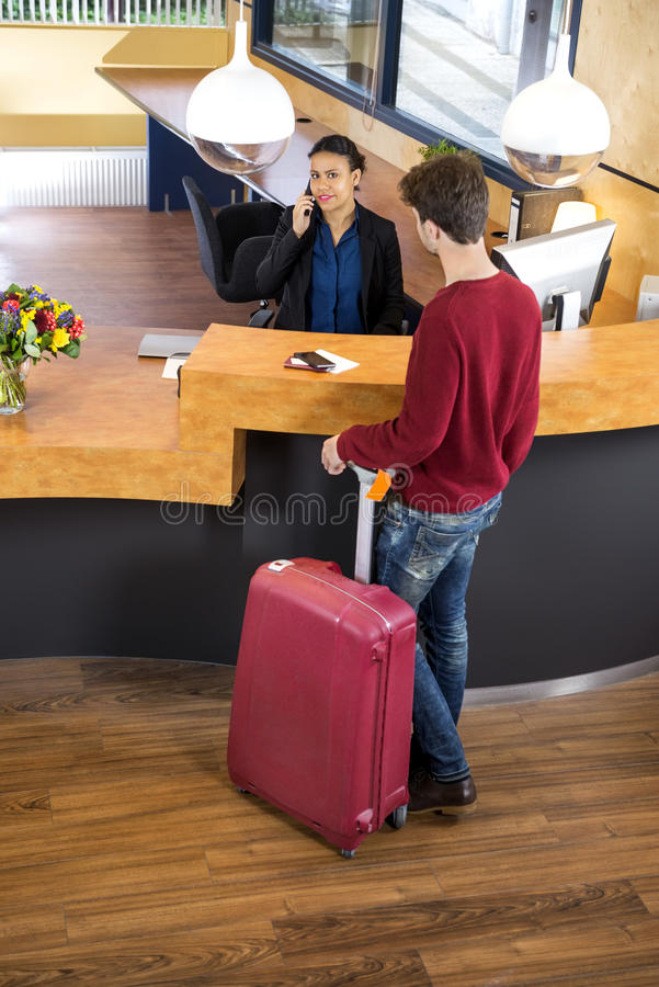 Man With Luggage At Hotel Reception. High angle view of men with luggage standing at hotel reception desk royalty free stock photography
