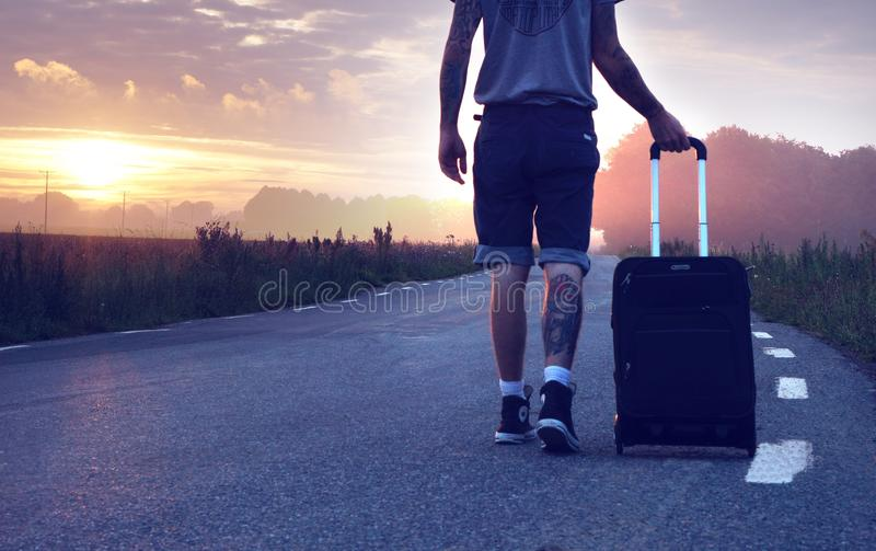 Man With Luggage on Road during Sunset stock photos