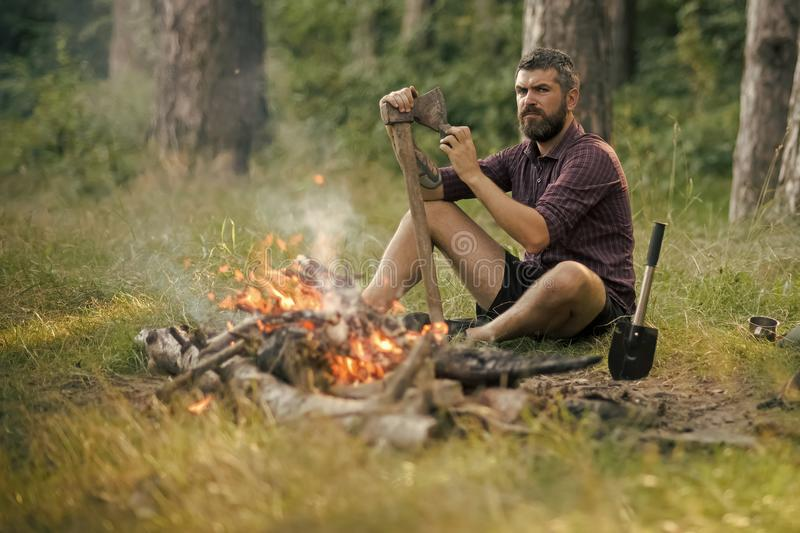 Man lumberjack with beard sharpen axe at bonfire. In forest on natural landscape. Logging and chopping concept stock images