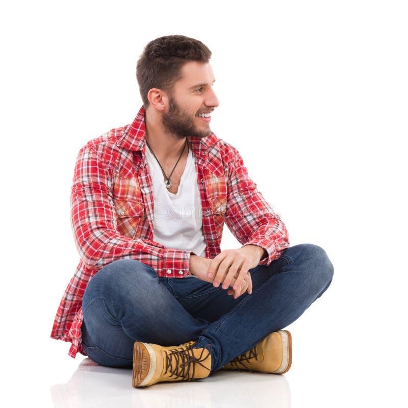 Man in lumberjack shirt sitting with legs crossed stock images