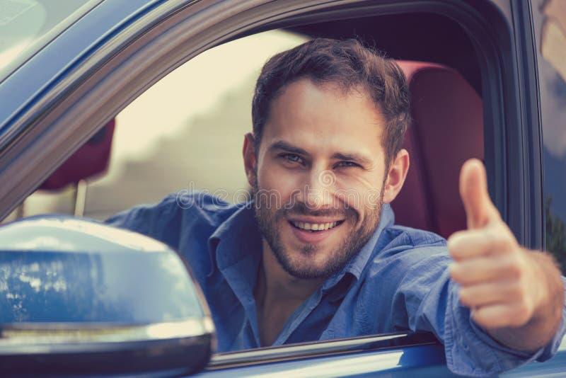 Man lyckliga le visningtummar för chauffören som kör upp sportbilen royaltyfri foto