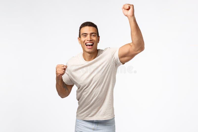 Man lyfter hand i hooray rörelse, jubilar efter favoritidrottslag Ta hand om en ung stark kille som håller på att le arkivfoton