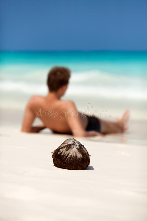 Man lying on a beach on a tropical island. Focus on coconut royalty free stock image