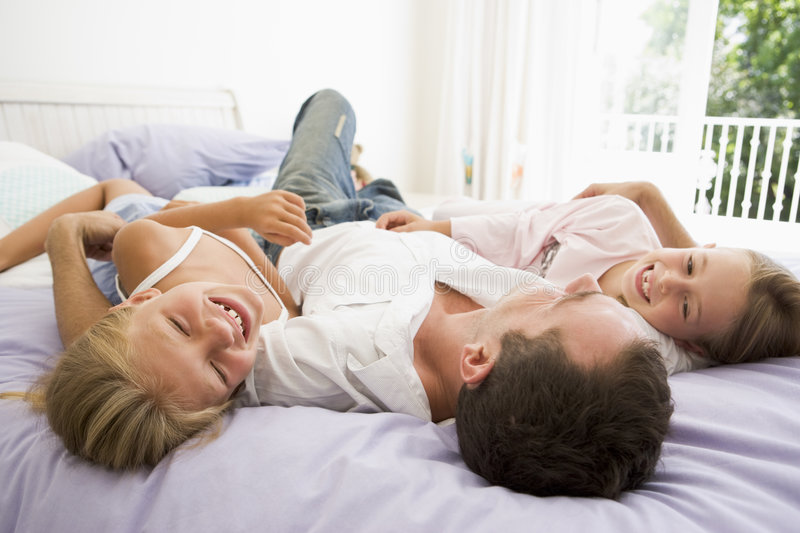 Man lying in bed with two young girls smiling royalty free stock image