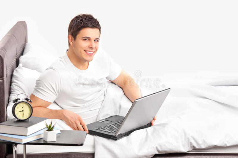 Man lying on a bed and working on a laptop stock image