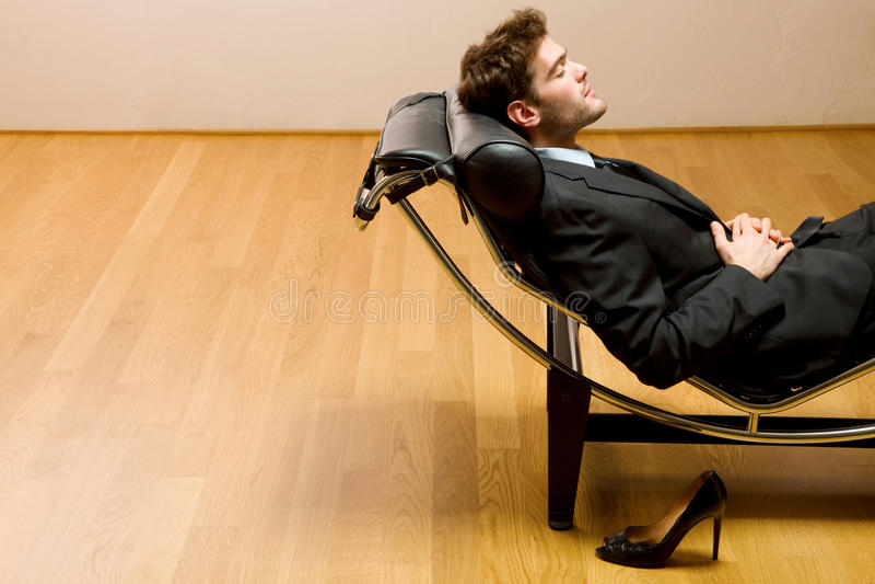 Man lying on chaise longue stock photos