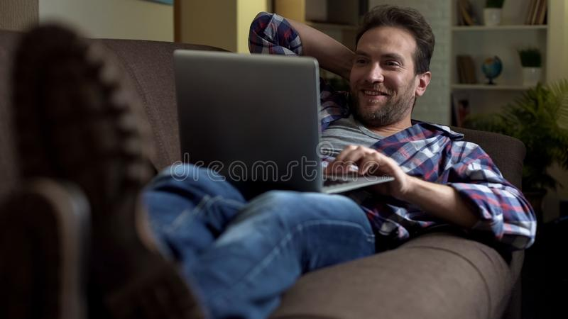 Man lying on couch with laptop, getting surprised at exciting news on screen stock images