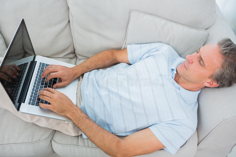 Man lying on couch typing on laptop. At home in living room royalty free stock image