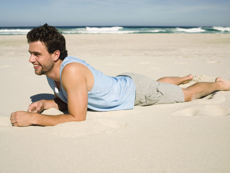 A man lying down on the beach. stock images