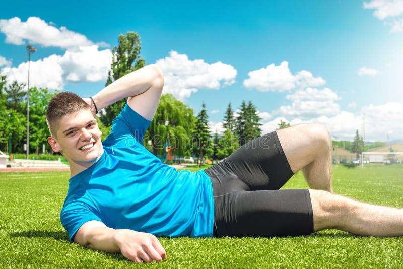 Man lying on grass field. stock photo