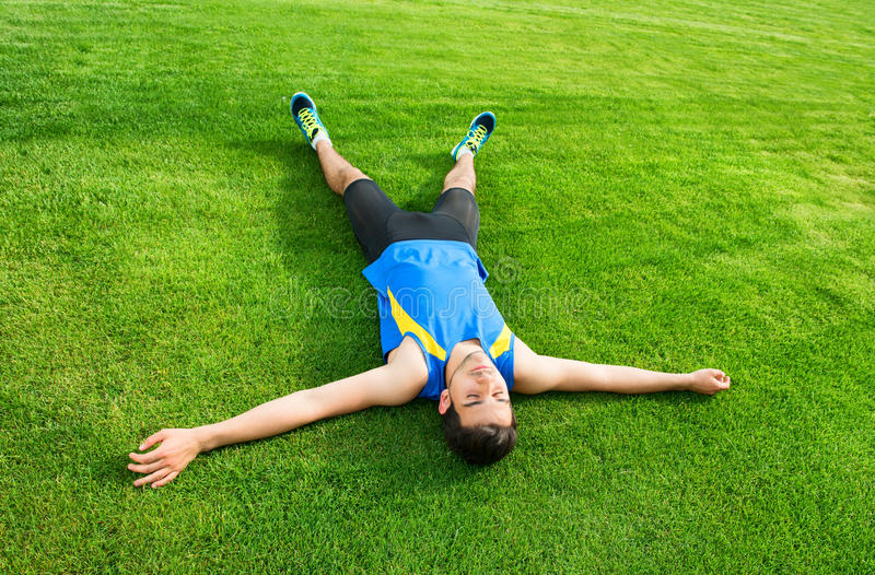 Man lying on the grass royalty free stock image