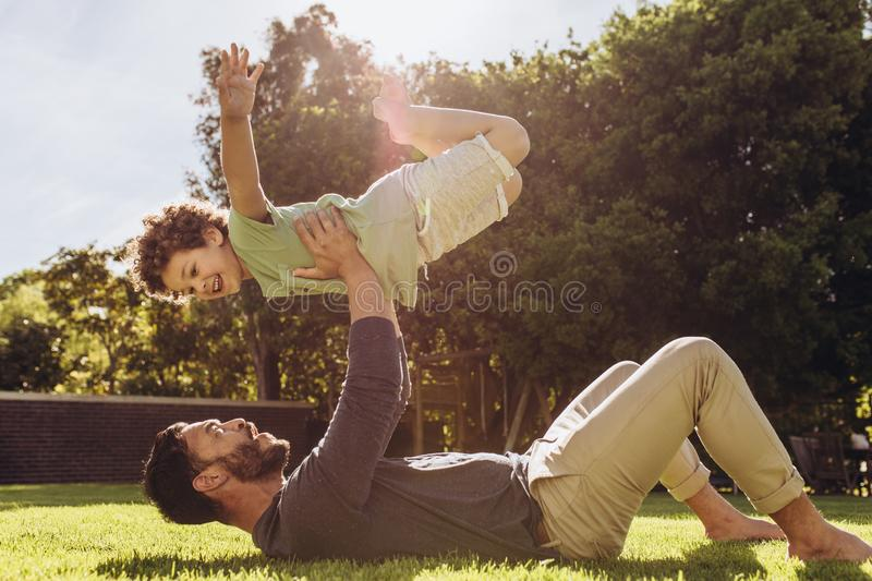 Father and son having fun playing in the park stock photos