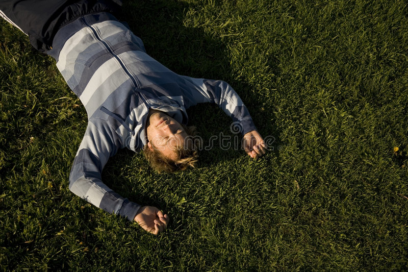 Man lying on a lawn stock images