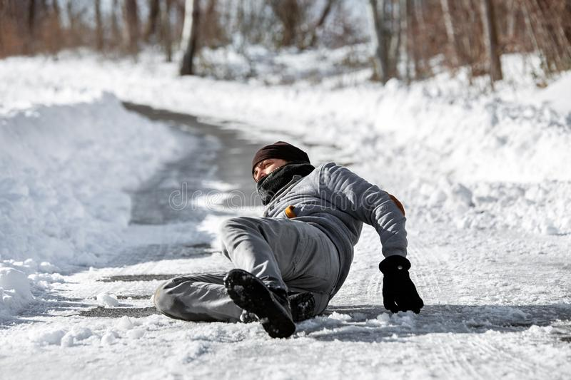 Man lying on the road, downfall and accident on winter season, black ice. Injured man lying on the road, downfall and accident on winter season, black ice stock images