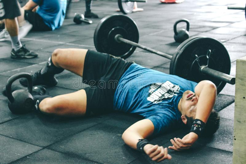 Man Lying on Rubber Mat Near Barbell Inside the Gym stock images