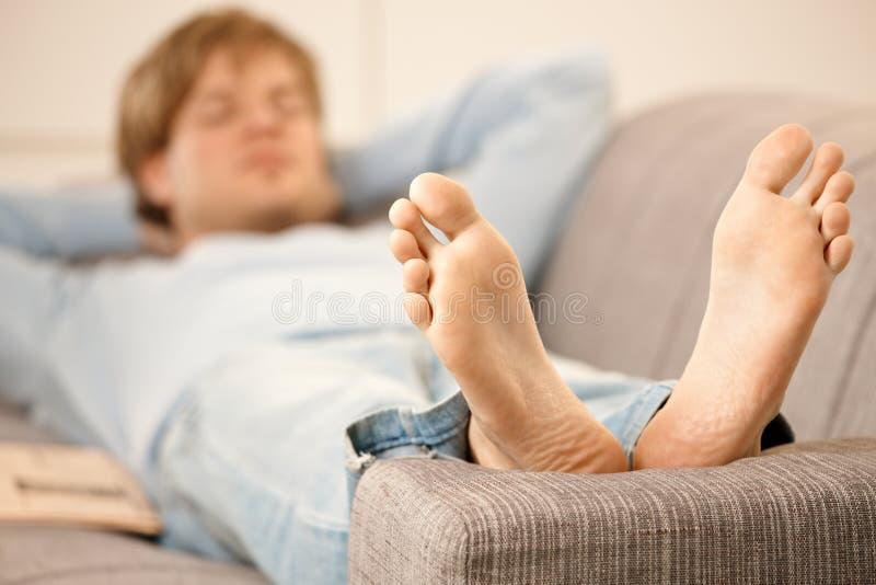 Man lying on sofa stock images
