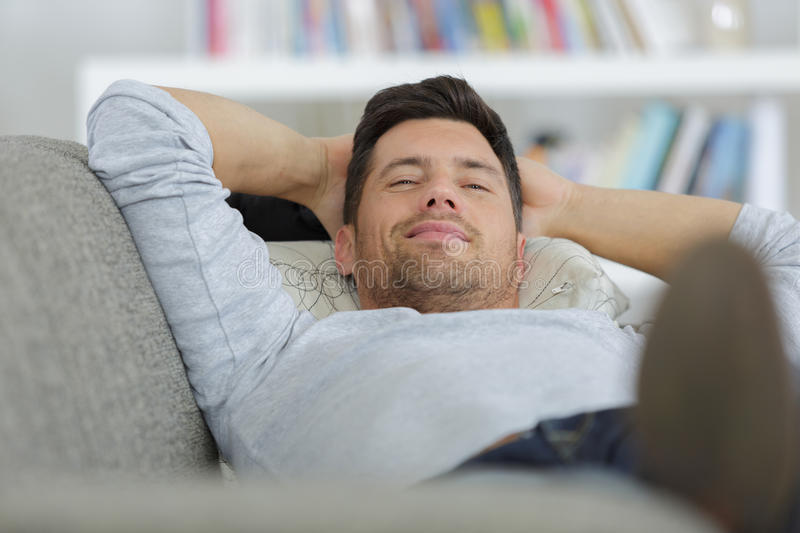 Man lying on sofa stock photo