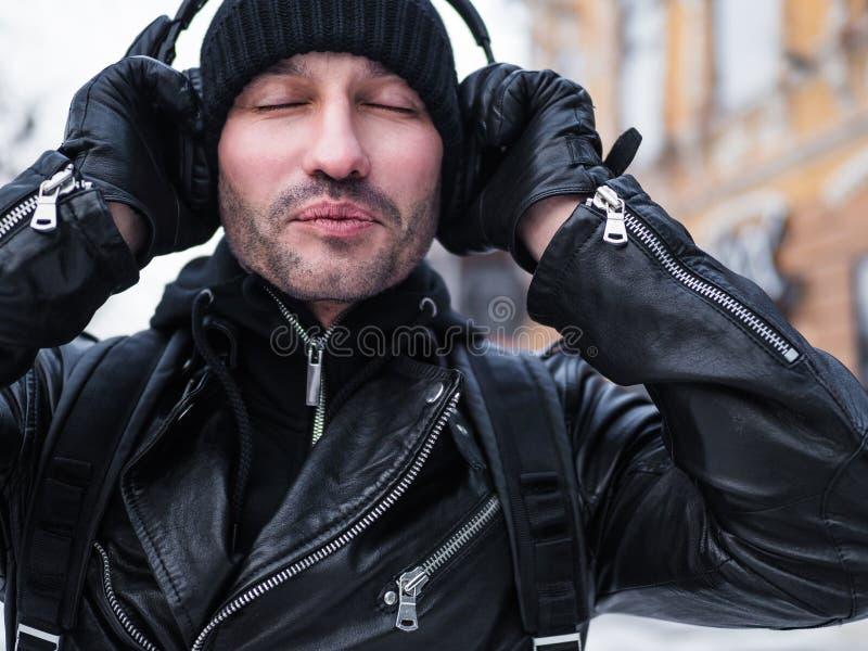 Man lyssnande musik via hörlurar i stree av New York Vinter Han stänger hans ögon royaltyfri foto
