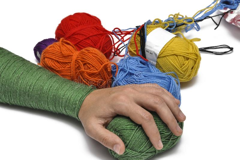 Man& x27; mão de s e fio colorido isolados em um fundo branco crochet Copie o espa?o fotografia de stock