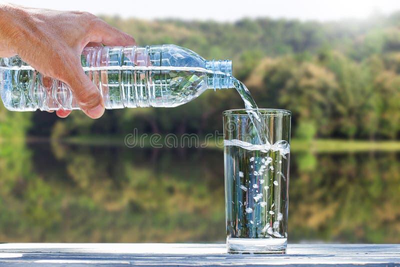 Man& x27; mão de s que guarda a água de garrafa bebendo e que derrama a água no vidro na tabela de madeira no fundo verde borrado foto de stock