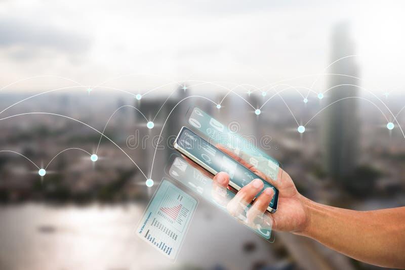 Man& x27; mão de s que guarda o smartphone com a multi tela transparente no fundo borrado da cidade imagem de stock