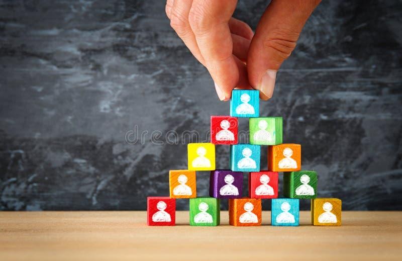 man& x27; mão de s que guarda uma parte superior da pirâmide de madeira dos blocos com ícones dos povos sobre a tabela de madeira imagens de stock royalty free