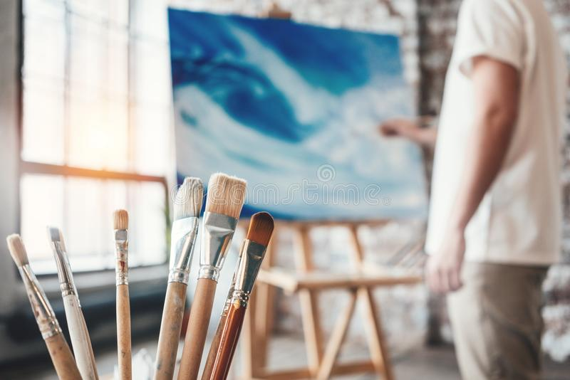 Man målaren som arbetar i seminarium med kanfas på staffli Borstar stänger sig upp på trätabellen i studio Signalljuseffekt royaltyfria foton