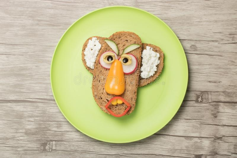 Man made with bread and vegetables on plate. Funny man made with bread, cucumber, pepper, radish, olive and bread. Creative idea to make a sandwich with kids stock image
