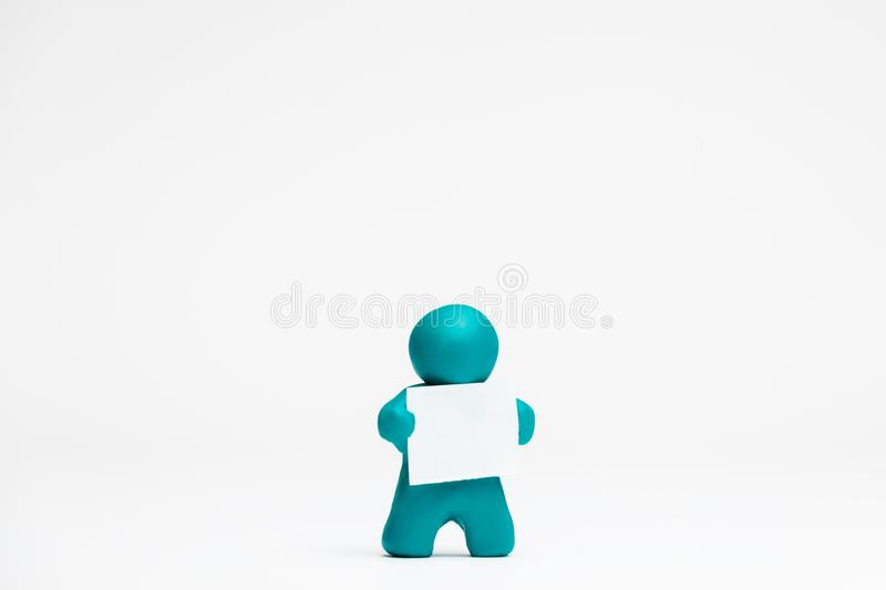 Man made from plasticine holding a blank sheet of paper on white background, aligned in the center. A man made from plasticine holding a blank sheet of paper on royalty free illustration
