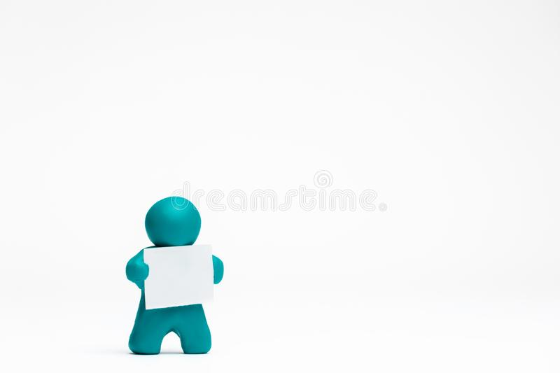 Man made from plasticine holding a blank sheet of paper on white background, aligned to the left. A man made from plasticine holding a blank sheet of paper on royalty free illustration