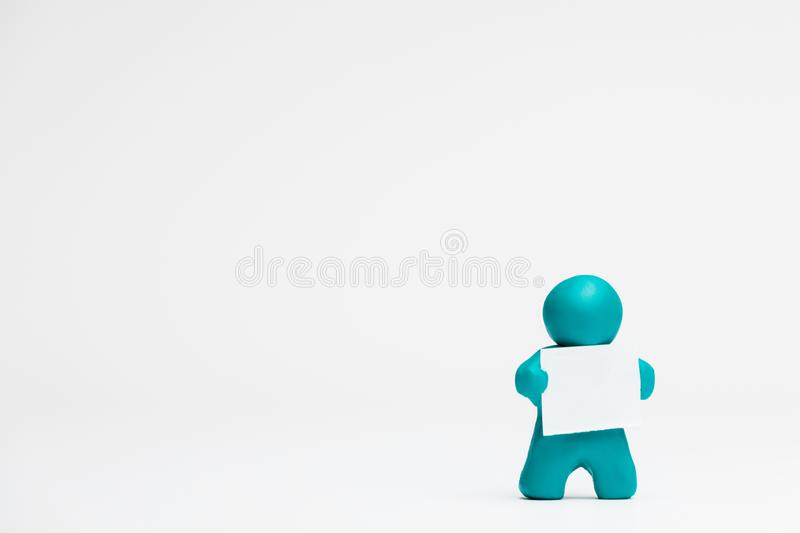 Man made from plasticine holding a blank sheet of paper on white background, aligned to the right. A man made from plasticine holding a blank sheet of paper on royalty free illustration