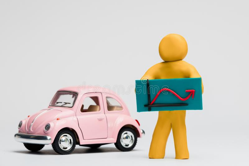 Man made from plasticine holding a graph with an arrow going up and down next to a pink car on white background, aligned in the stock photos