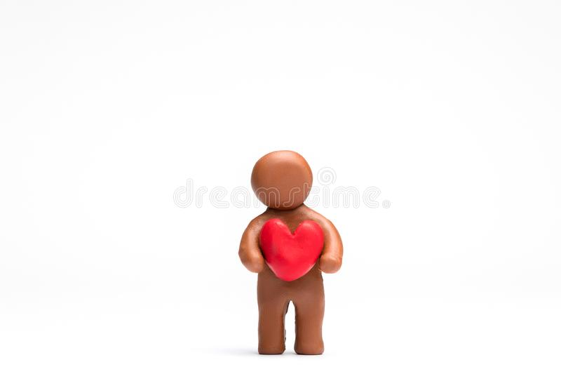 Man made from plasticine holding a heart on white background, aligned in the center stock image