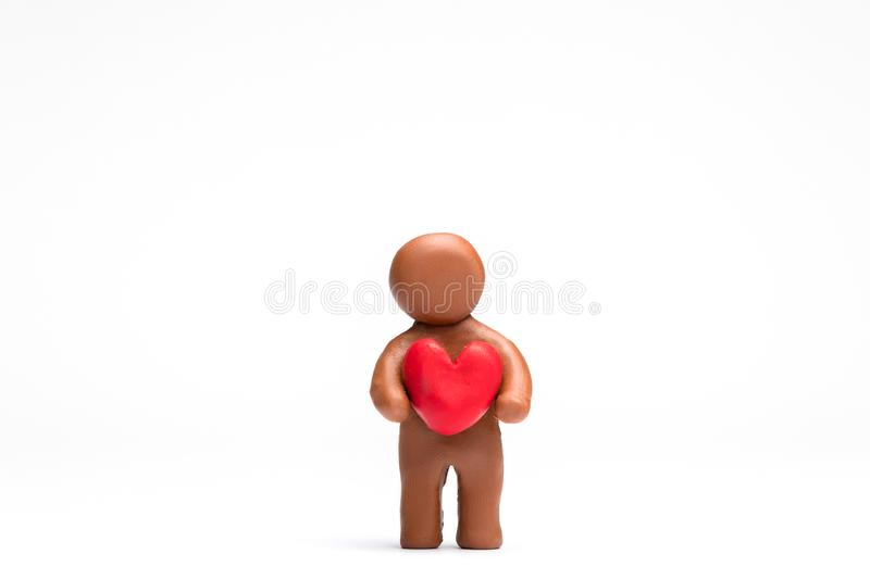 Man made from plasticine holding a heart on white background, aligned in the center stock images