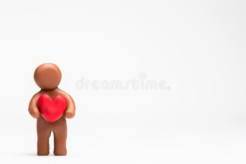 Man made from plasticine holding a heart on white background, aligned to the left royalty free stock photo