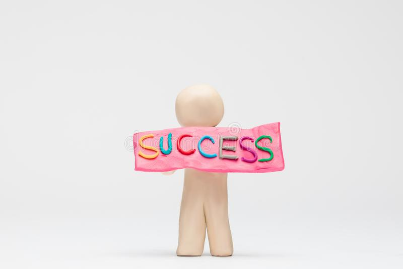 Man made from plasticine holding a poster with the word success on white background, aligned in the center royalty free stock photography