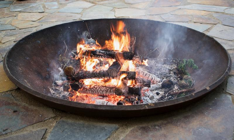 Garden Fire pit At Sunset. Man made upscale garden fire pit on a warm summer evening stock image